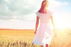 Mujer joven en el vestido blanco que camina adelante en campo Imagen de archivo