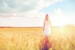 Mujer joven en el vestido blanco que camina adelante en campo Imágenes de archivo libres de regalías