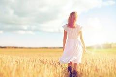 Mujer joven en el vestido blanco que camina adelante en campo Fotografía de archivo