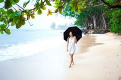Mujer joven en el vestido blanco que camina en la playa que sostiene el paraguas Imagenes de archivo