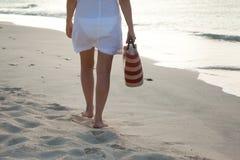 Mujer joven en el vestido blanco que camina solamente en la playa Imagen de archivo