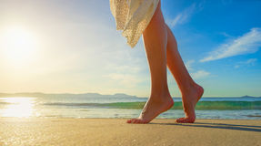 Mujer joven en el vestido blanco que camina solamente en la playa en el sol Fotos de archivo