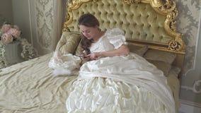 Mujer joven en el vestido de bola que miente en la cama y los textos adornados oro por el teléfono celular La muchacha utiliza el metrajes