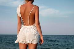 Mujer joven en el vestido del verano que se coloca en una playa y que mira al mar Imagen de archivo