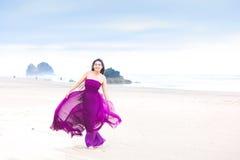 Mujer joven en el vestido magenta que fluye que se coloca en la playa Fotos de archivo