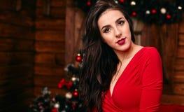 Mujer joven en el vestido rojo en la Navidad adornado Foto de archivo libre de regalías