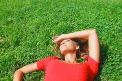 Mujer joven en el vestido rojo que miente en hierba Imagenes de archivo