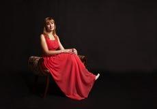 Mujer joven en el vestido rojo que se sienta en una silla Imágenes de archivo libres de regalías