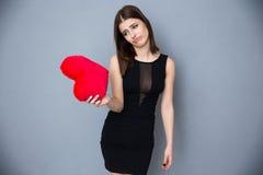 Mujer joven en el vestido sexy que mira en corazón rojo Imagen de archivo libre de regalías