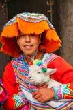 Mujer joven en el vestido tradicional que sostiene el cordero en la calle de C Imagenes de archivo