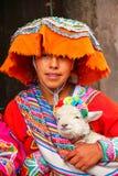 Mujer joven en el vestido tradicional que sostiene el cordero en la calle de C Imagen de archivo
