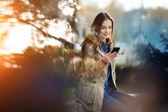 Mujer joven en envío de mensajes de texto de la ropa casual que disfruta de día de primavera al aire libre Imagen de archivo