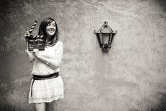 Mujer joven en estilo del hippie 70s que sonríe con negro del clapperboard Imagenes de archivo