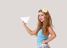Mujer joven en estilo modelo con el avión de papel imagen de archivo