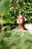 Mujer joven en flor del jazmín Fotos de archivo