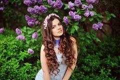 Mujer joven en flores de la lila foto de archivo