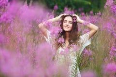 Mujer joven en flores rosadas Foto de archivo libre de regalías