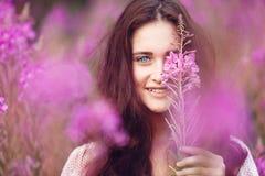 Mujer joven en flores rosadas Foto de archivo