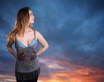 Mujer joven en fondo de la puesta del sol Foto de archivo
