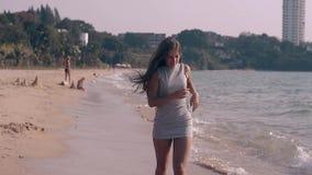 Mujer joven en funcionamientos del vestido a lo largo de la cámara lenta de la playa tropical