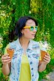 Mujer joven en gafas de sol amarillas con un helado Foto de archivo libre de regalías