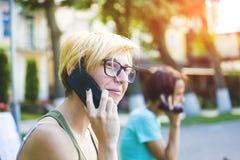 Mujer joven en gafas de sol elegantes que habla en el teléfono móvil Fotos de archivo libres de regalías