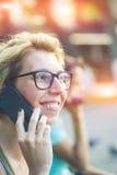 Mujer joven en gafas de sol elegantes que habla en el teléfono móvil Foto de archivo