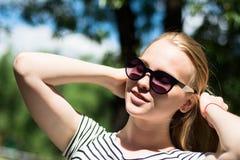 Mujer joven en gafas de sol en un fondo de la naturaleza Foto de archivo libre de regalías