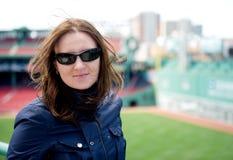 Mujer joven en gafas de sol que visita un parque del béisbol Foto de archivo libre de regalías