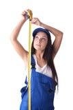 Mujer joven en guardapolvos con una cinta de medición Foto de archivo libre de regalías