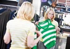 Mujer joven en hacer compras de la ropa de las camisas Imagenes de archivo