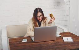 Mujer joven en hacer compras en línea de los vidrios en casa Imagen de archivo libre de regalías