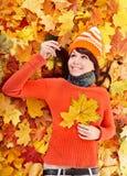 Mujer joven en hojas anaranjadas del otoño. Foto de archivo