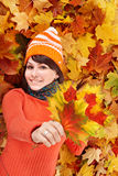 Mujer joven en hojas anaranjadas del otoño. Fotos de archivo libres de regalías
