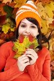 Mujer joven en hojas anaranjadas del otoño. Imágenes de archivo libres de regalías