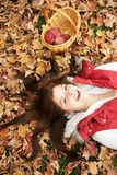 Mujer joven en hojas de la caída Imagenes de archivo