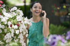 Mujer joven en jardín con el teléfono celular Foto de archivo libre de regalías