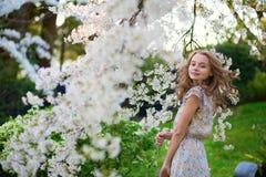 Mujer joven en jardín floreciente de la cereza Fotografía de archivo