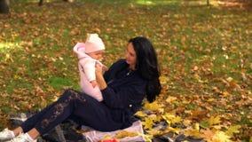 Mujer joven en jugar negro con el bebé en parque almacen de metraje de vídeo