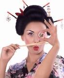 Mujer joven en kimono japonés con los palillos y el rollo de sushi Foto de archivo