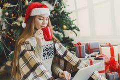 Mujer joven en línea en el ordenador portátil en el interior de la Navidad Foto de archivo libre de regalías
