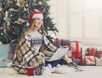 Mujer joven en línea en el ordenador portátil en el interior de la Navidad Imagen de archivo libre de regalías