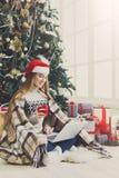 Mujer joven en línea en el ordenador portátil en el interior de la Navidad Foto de archivo