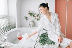 Mujer joven en la albornoz blanca de n, interior del cuarto de baño foto de archivo libre de regalías