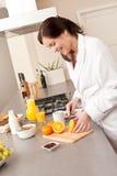 Mujer joven en la albornoz que corta la naranja en cocina Foto de archivo libre de regalías