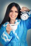 Mujer joven en la albornoz que sostiene un despertador y una taza de café Fotos de archivo libres de regalías