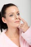 Mujer joven en la albornoz rosada que aplica una crema en su nariz, mejillas y frente Imagen de archivo libre de regalías