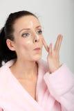 Mujer joven en la albornoz rosada que aplica una crema en su nariz, mejillas y frente Imagenes de archivo