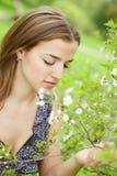Mujer joven en la alineada que se relaja en jardín Fotos de archivo libres de regalías