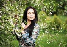 Mujer joven en la alineada que se relaja en jardín Imágenes de archivo libres de regalías